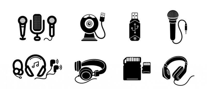 Icon set in black of digital gadgets with speakers, microphones, headphones, camera, smartphone, digital tablet, desktop computer, earpieces, memory stick, mouse, microphone isolated on white background